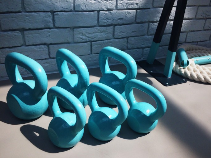 Blue weights up against a wall at a gym