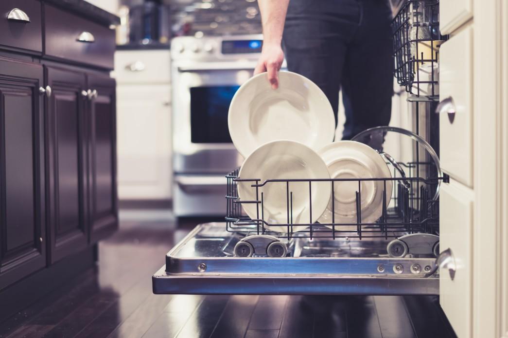 Man loading a dishwasher in a kitchen