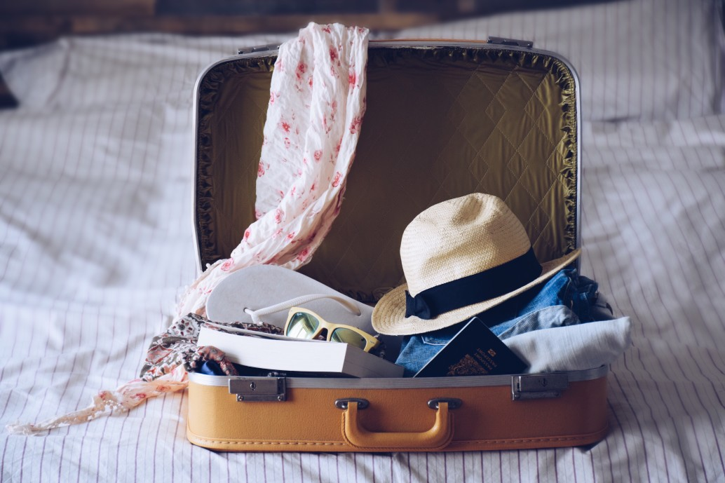 A briefcase on a bed full of clothes and luggage ready for a summer vacation