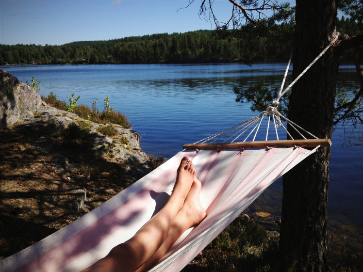 Woman laying on a hammock outside by a lake